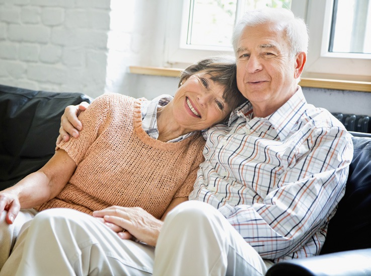 Elderly couple embracing on a couch