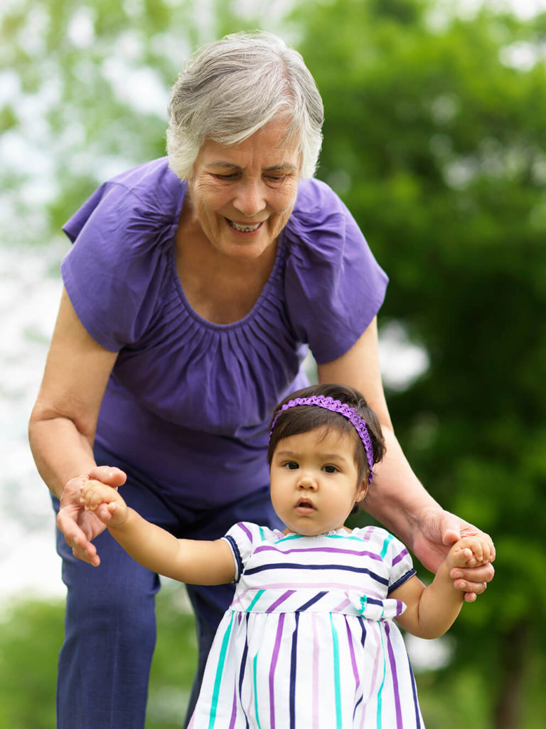 Older woman holding hands with a walking child